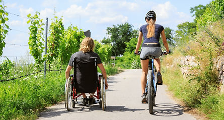 Photo of a smooth asphalt path with green grape vines on the left and a rock wall with greenery on the right. Heading away from the camera is a male with blond hair wheeling a wheelchair on the left  side of the path. A blond long haired woman with helmet, is on his right alongside him riding a bike on the right side of the path. The woman is wearing a blue short sleeved shirt, blue shorts and runners. The sky is blue with clouds and the sun casts their shadows on the path.