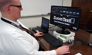 Photo - On the left side of the photo a male employee in a white shirt with a black layard around his neck is seated facing a computer workstation. He is wearing dark glasses. He is middle aged. On the black computer screen in large white font are the words Zoom Text. The computer screen is sitting on two white boxes. To the man's left side is a small laptop sitting on the desk, the keyboard sits on the desk about 4 inches in front of him. In the background, a wall mounted white board sits on a white wall. The employee's hands are resting on the desk and mouse.
