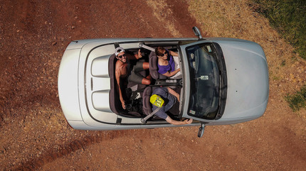 Aerial photo of an open roof cabriolet with people inside.