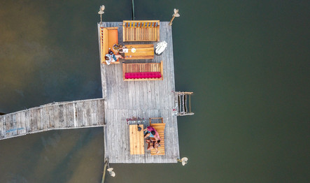 Aerial photo of a wooden pier with people on sofas