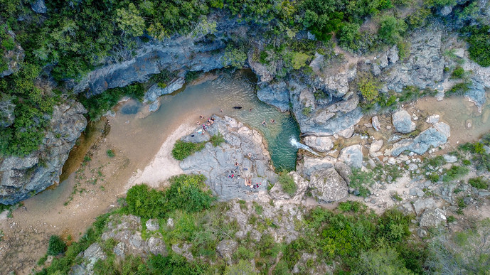 Aerial photo of a group of friends having fun in the waterfall / river
