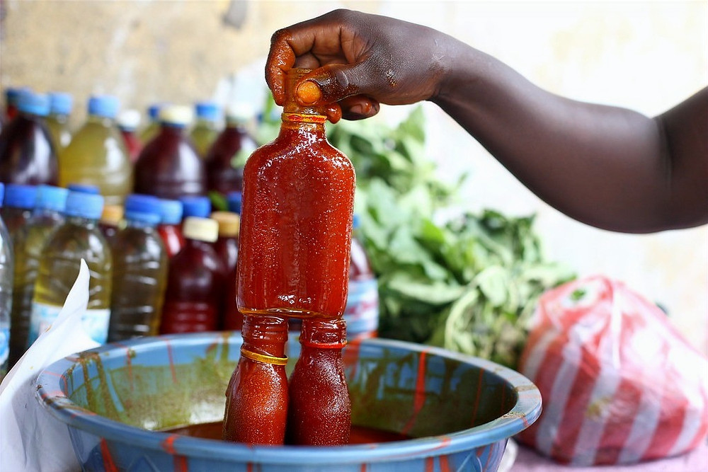 Hand of a marketer holding a bottle of palm oil