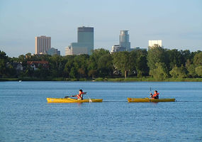 Two people padding yellow kayaks across