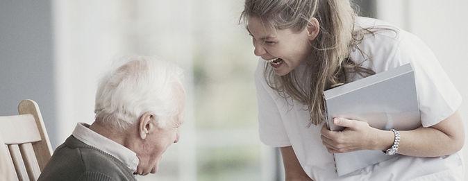Elderley man and female carer laughing