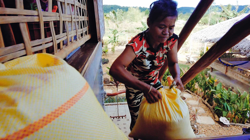Maria, transporte un sac de riz au lodge Himulak à Palawan