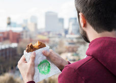a mand eating a pie from Proper Pie at Libbie Hill in Richmond, VA