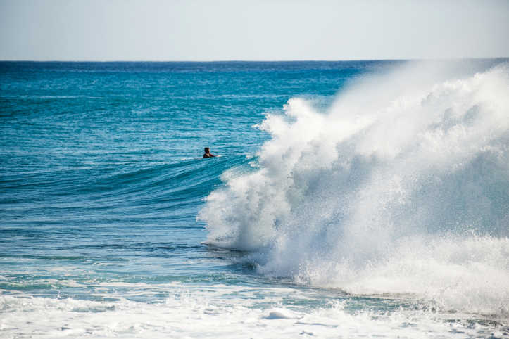 a man surfing at Ka'ena Point in Oahu Hawaii