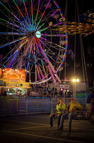 a young couple sitting on a ride near the ferris wheel at the State Fair of Virginia
