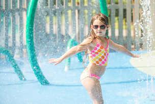 a girl playing in a sprinkler at Lewis Ginter Botanical Garden