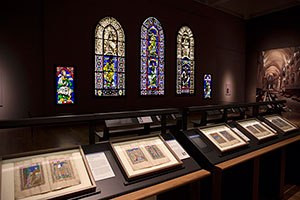 Image: Canterbury and St. Albans exhibition at the Getty Center. Foreground: St. Albans Psalter, about 1130, Alexis Master. Tempera and gold on parchment. Dombibliothek Hildesheim. Background: Panels from the Ancestors of Christ Windows, Canterbury Cathedral, England, 117880. Colored glass and vitreous paint; lead came. Courtesy Dean and Chapter of Canterbury