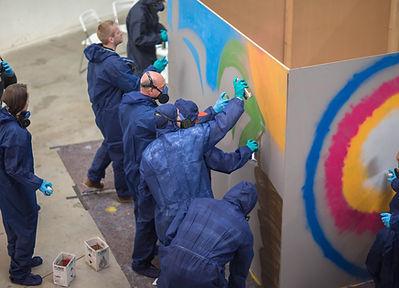Die Teilnehmer können in Teams an Wänden sprühen.