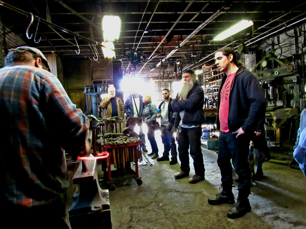 """Tour visitors watch Daniel Lapidow (aka """"the Hebrew Hammer"""") demonstrate historic blacksmithing techniques, AAD 2018. Photo: Rob Keephart."""
