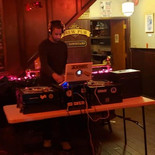 DJ Flea Market concentrates on his set at First Fridays @ the Mill Hill Saloon. Photo via First Fridays Facebook.