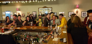 First Fridays @ Mill Hill Saloon - photo via First Fridays FB. Happy people make faces around the bar.