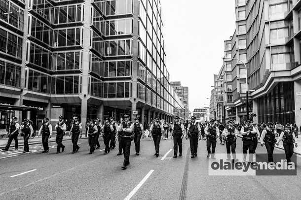 Police officers march in a line from Hyde Park to Parliament square