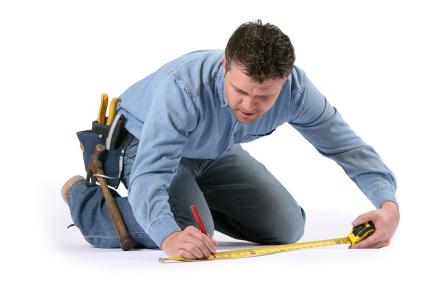 Man on knees using tape measure