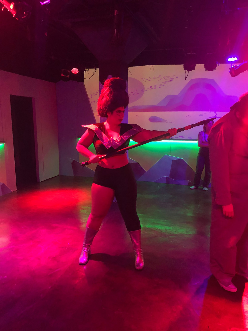 Barbette (Sarah Bacinich) threatens a manslave with her spear.