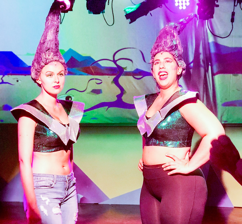Two Wild Women from the mysterious Planet Won- go stand and joke as a light cue is built around them.