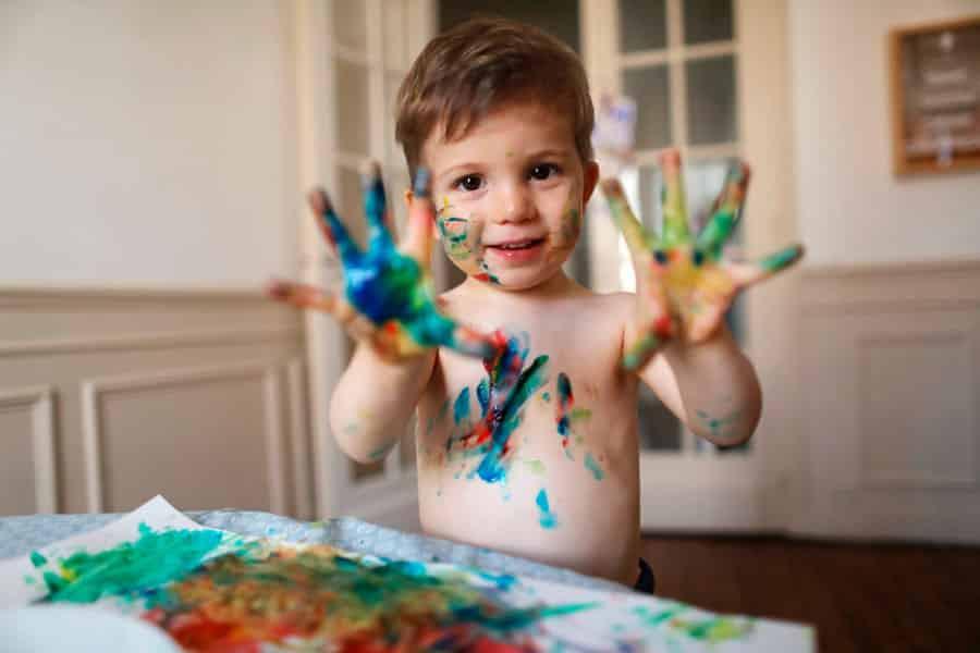 criança com as mãos sujas de tinta