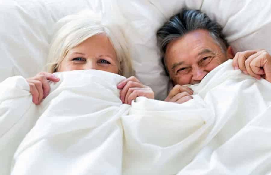 casal terceira idade deitado na cama, com o corpo e metade do rosto coberto