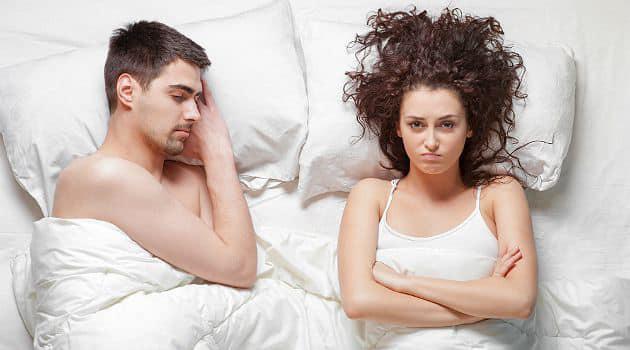 casal deitado na cama. homem dormindo e mulher com raiva