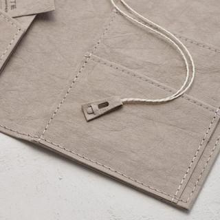 紙ならではの意匠。  栞ひも先端の愛嬌ある表情。  秘密は、針無しホチキス。 工具として使用できたのは素材が丈夫な紙だからこそ。  他にも、栞ひもを通す穴部分や栞本体に使っています。