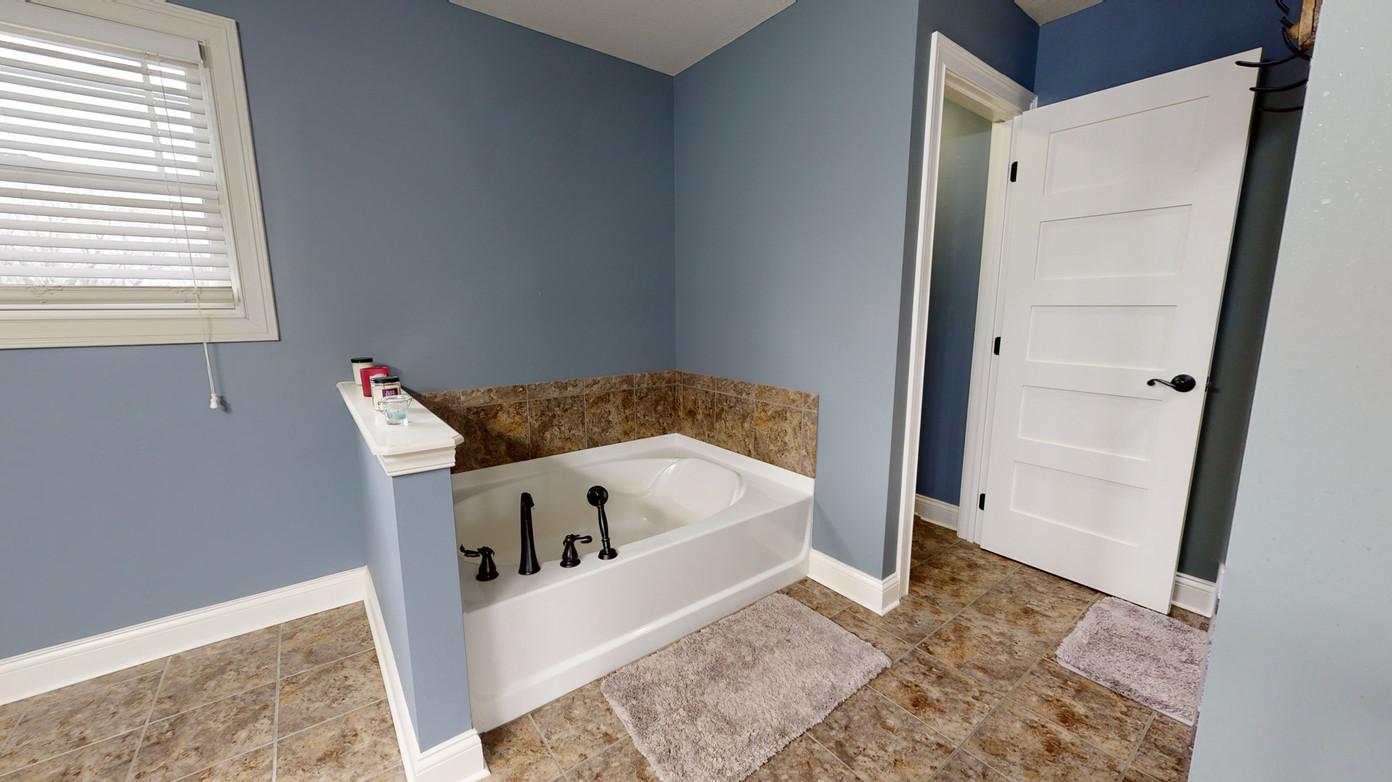 Bathroom with brown tiled floors and blue-grey paint