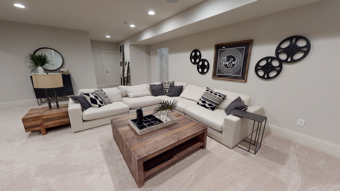 Beautiful white sectional couch in a basement tv entertainment area. White leather couch with natural wood tables and brand new carpet