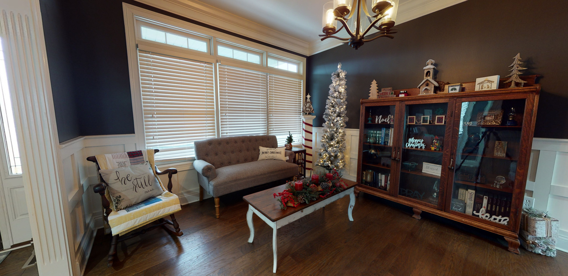 Cozy seating area with wooden half wall glass bookshelf and dark natural wood floors