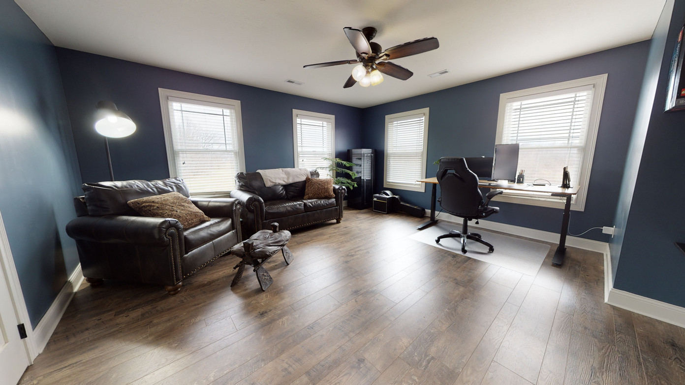 Upstairs open office with wood floors, black couches, quality captains office chair, and dark blue walls