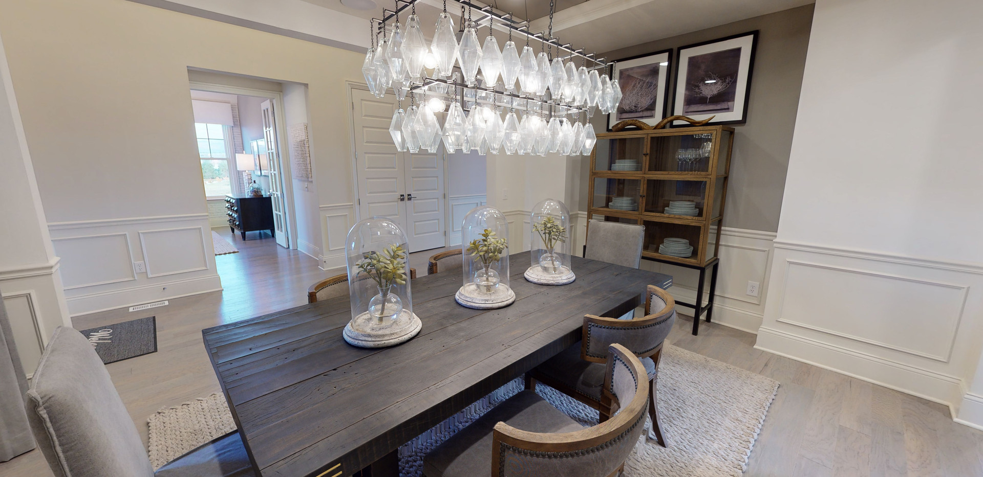 grey dining room area with large chandelier and grey chairs around a natural wood grey table