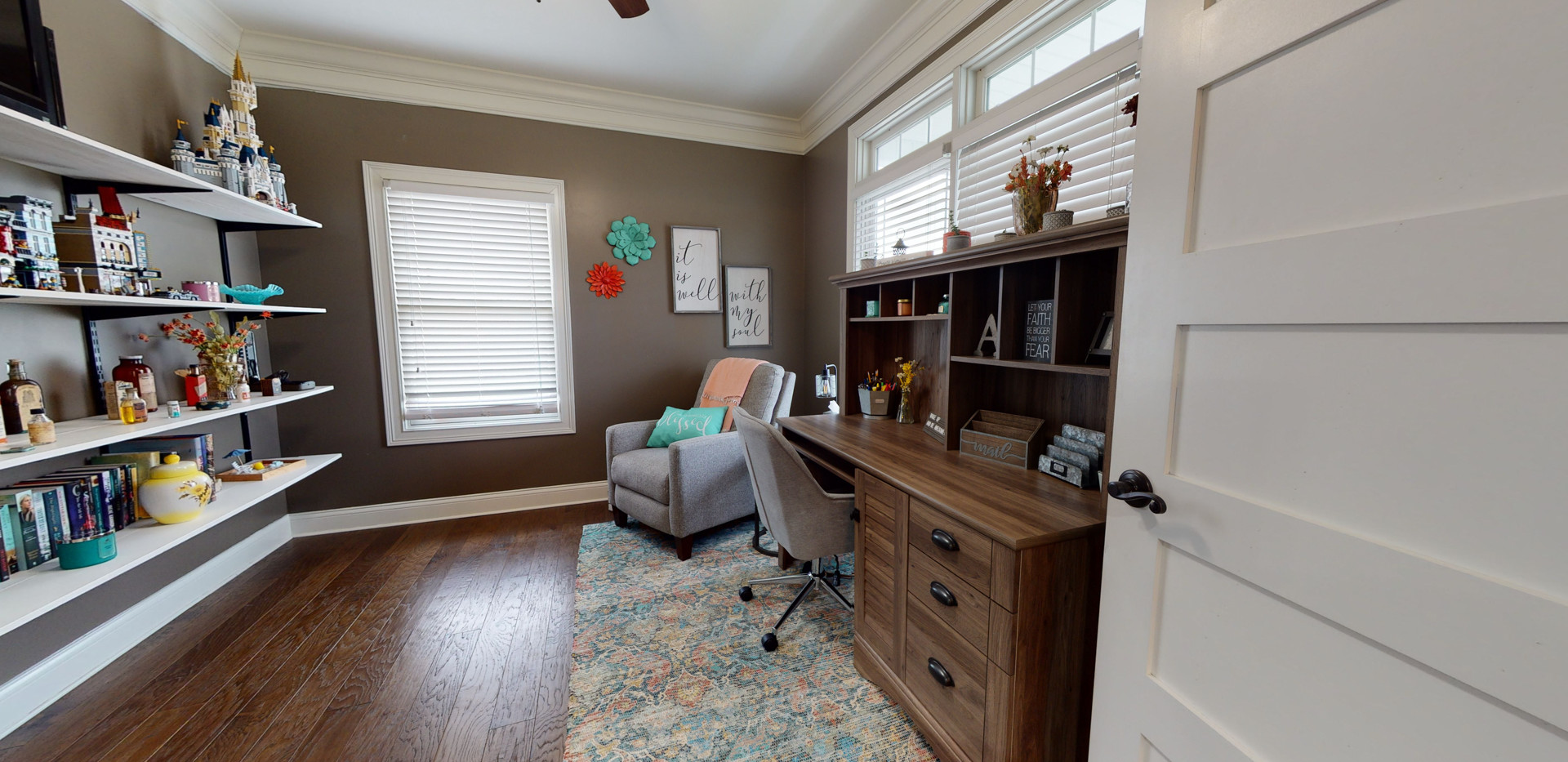 Dark wood floors in office area complete with grey recliner, grey desk chair, and large shelves for collectibles.