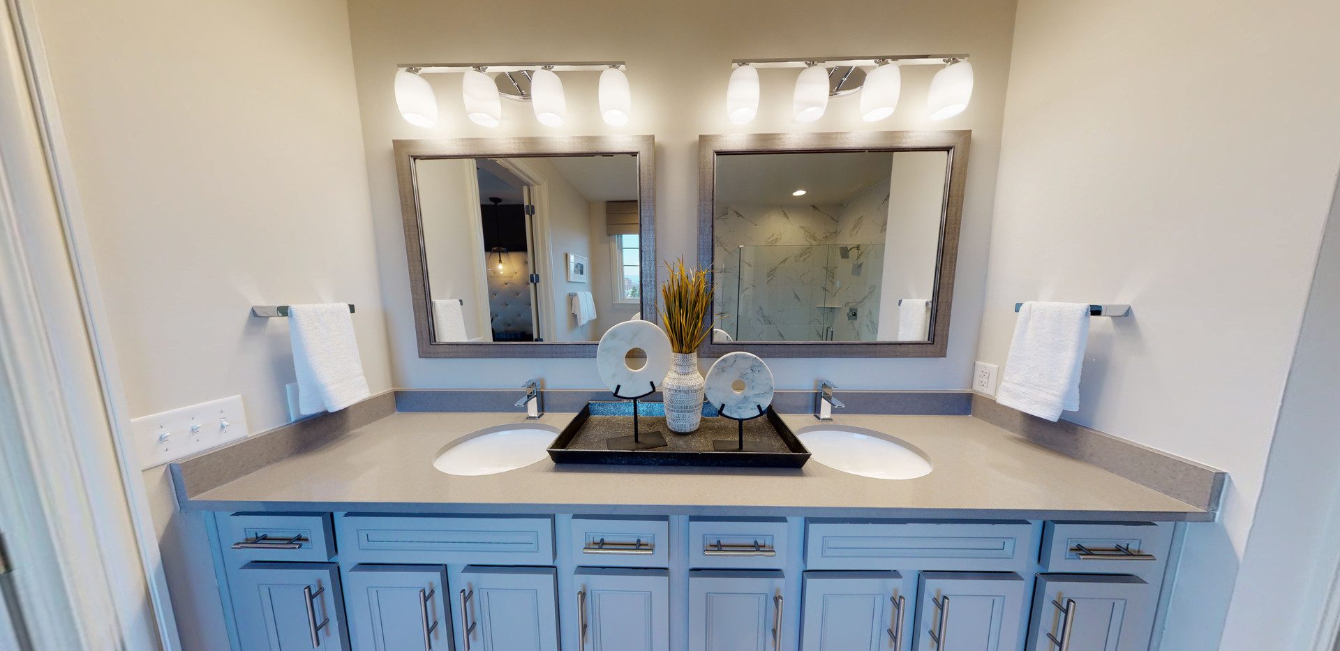 Close up of vanity in a white marble bathroom with double grey vanity, double mirrors with grey frames, and large walk-in closet attached