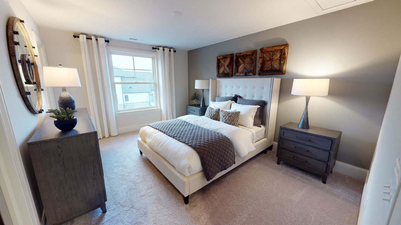 Guest bedroom with white bed, grey accent blanket, and a 3-piece bedroom furniture set made of grey natural wood