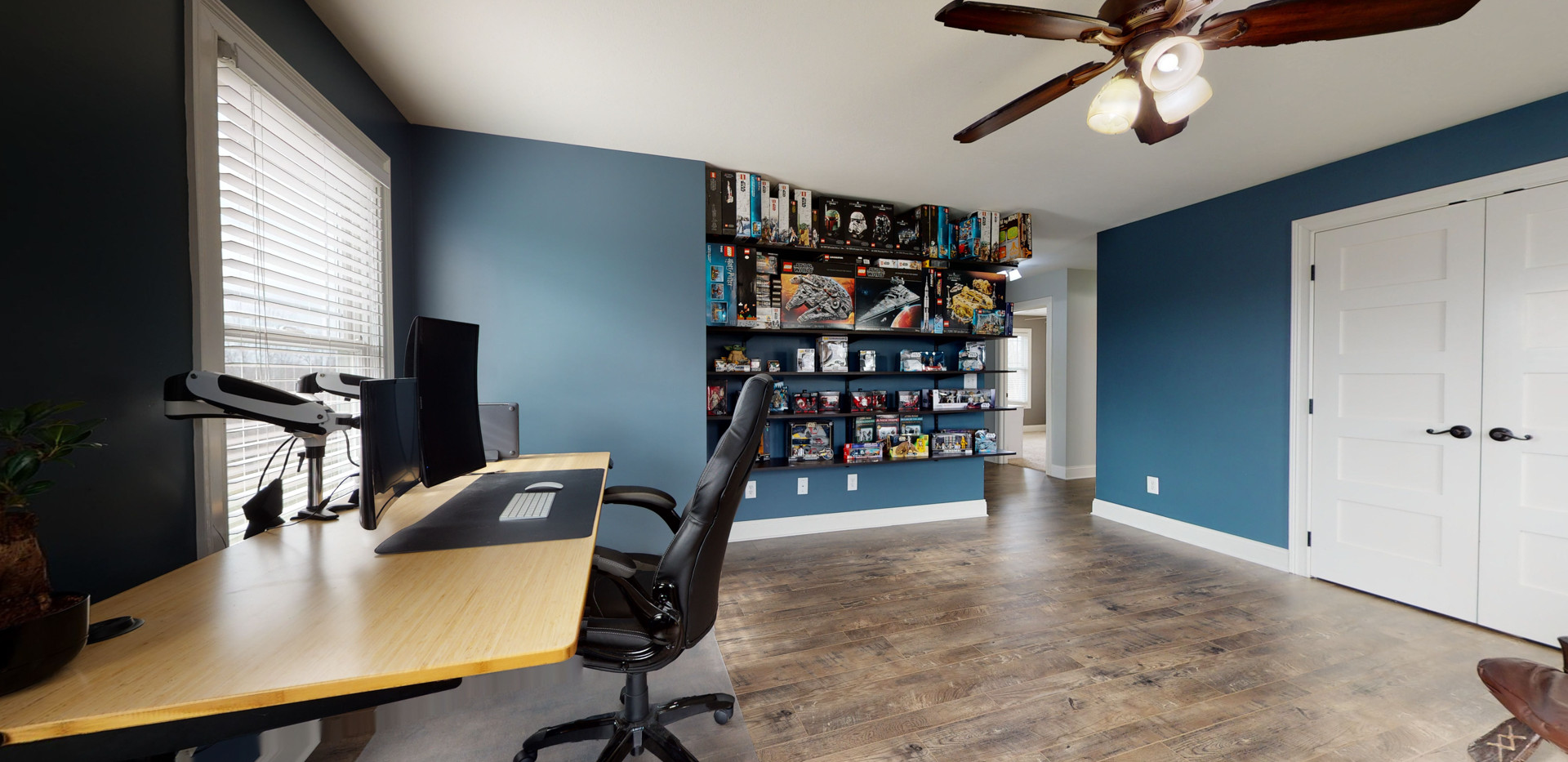 Upstairs open office with wood floors, black couches, quality captains office chair, and dark blue walls. Also shows shelves full of collectible items