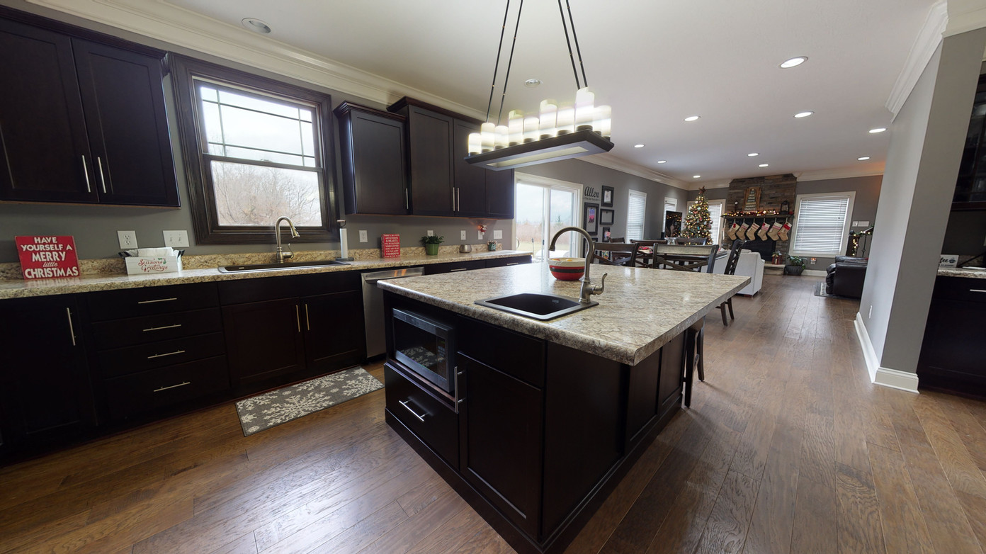 Kitchen real estate photography showing light natural wood, painted black cabinets, and large island prep area with sink and off white granite countertops