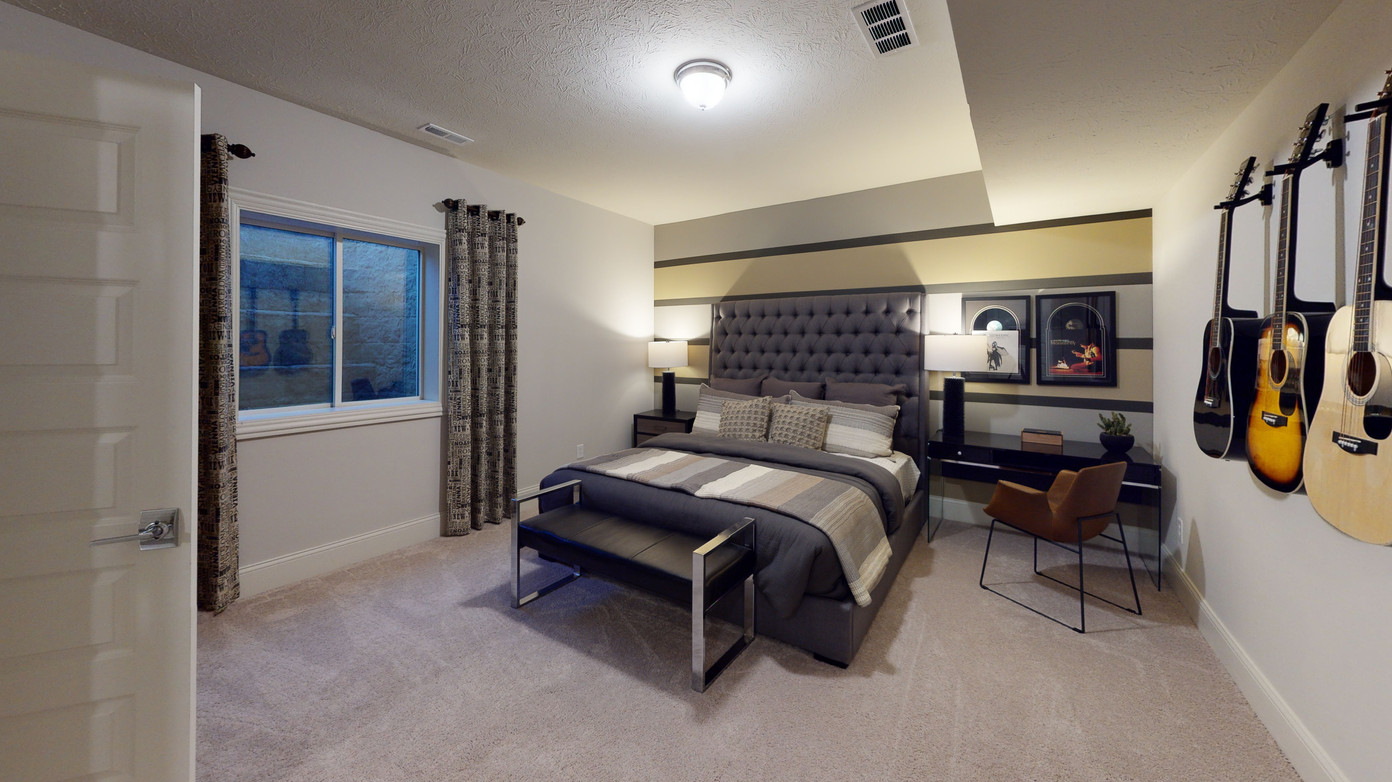 Nashville inspired guest bedroom in noblesville, IN complete with guitars on walls, framed vinyl records, and brown leather desk chair