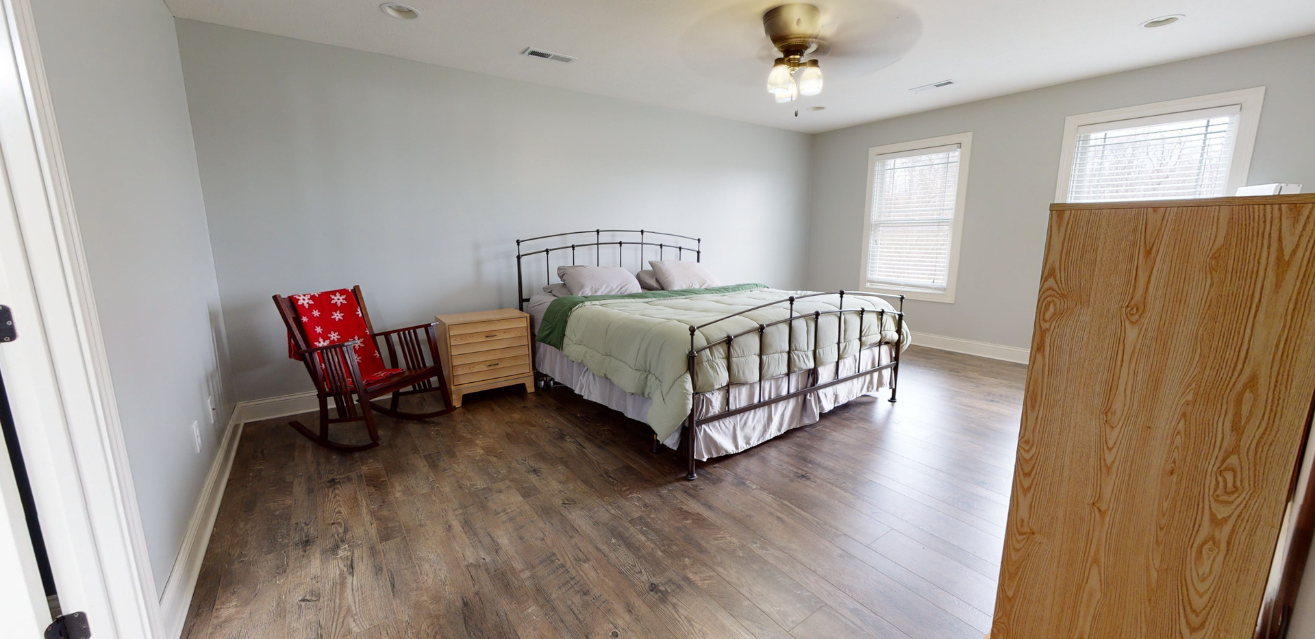 Simple master bedroom with sand colored natural wood floors