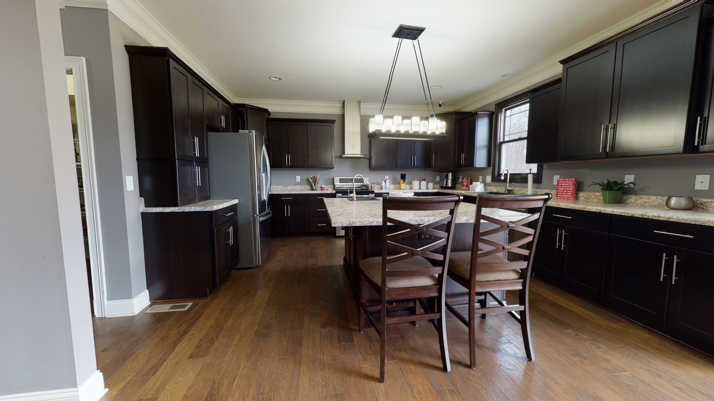Different angle of kitchen real estate photography showing light natural wood, painted black cabinets, and large island prep area with sink and off white granite countertops
