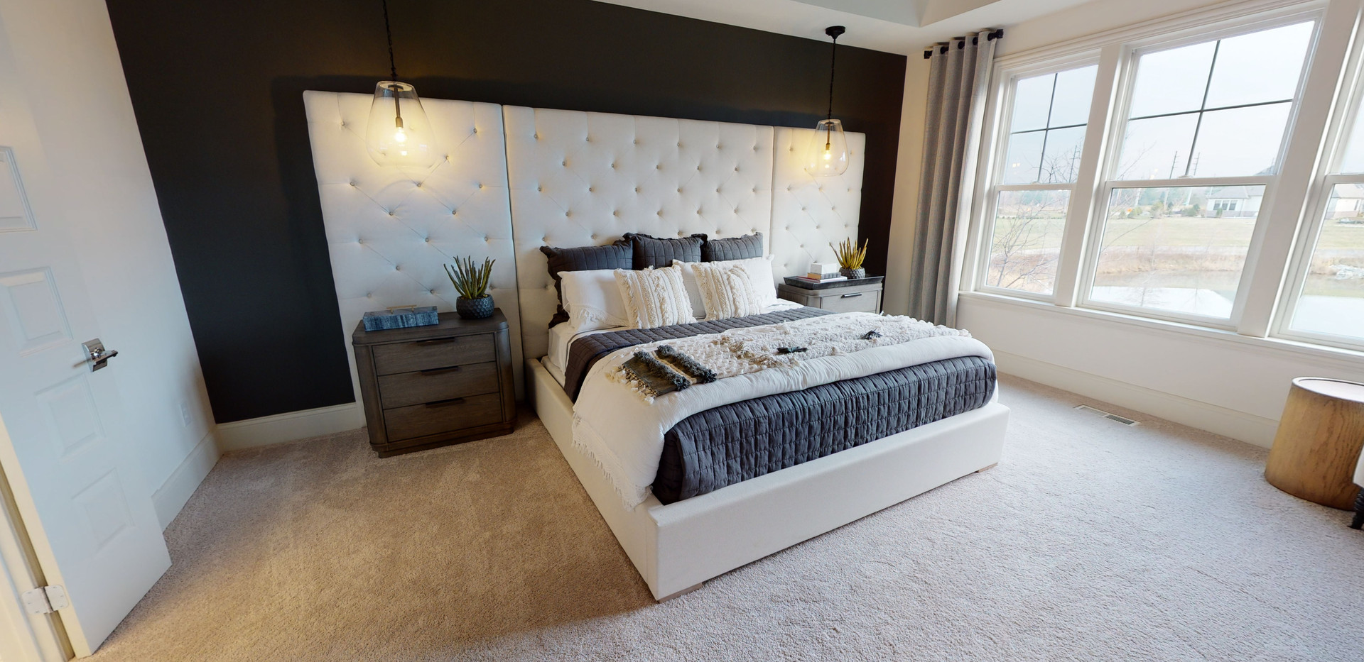 White master bedroom with white queen size bed in front of an oversized white headboard. Black accent wall behind headboard