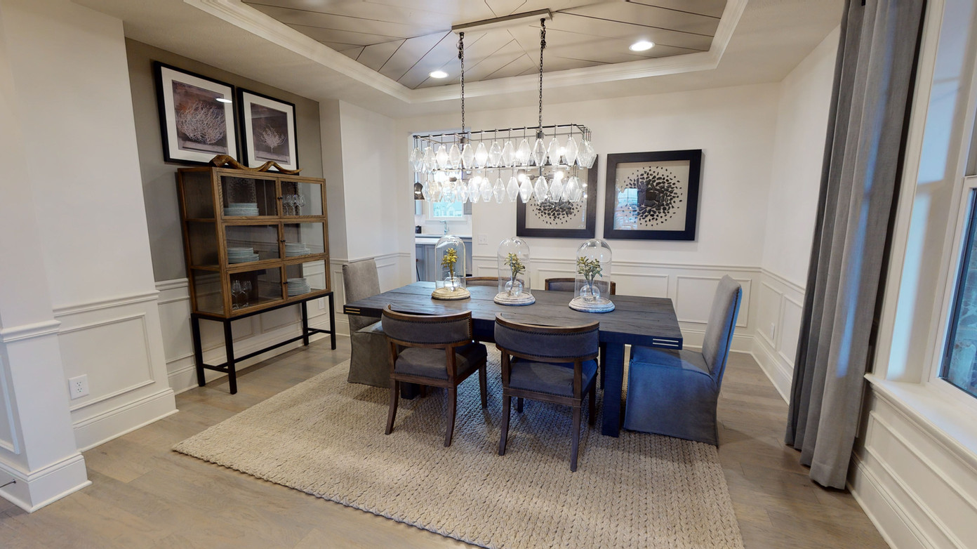 Wide angle photo of grey dining room area with large chandelier and grey chairs around a natural wood grey table