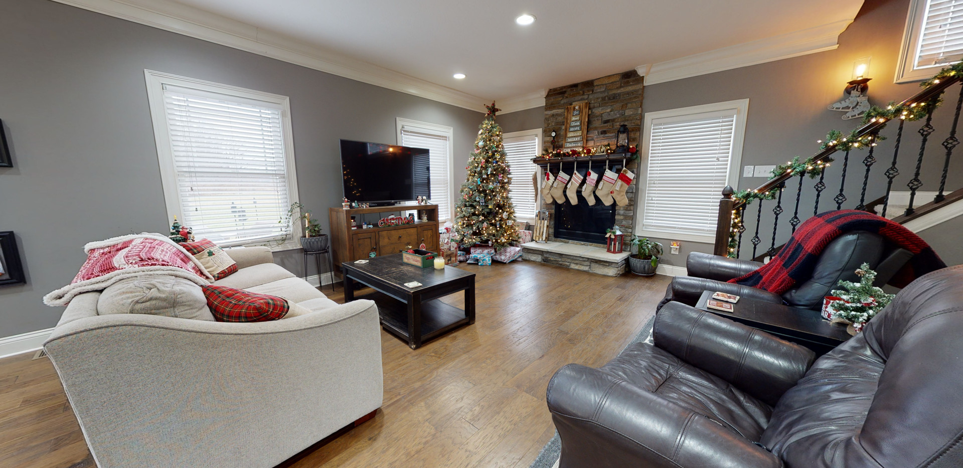 Cozy livingroom with christmas decorations including stockings hung on stone fireplace, tv, black chairs, and a white couch