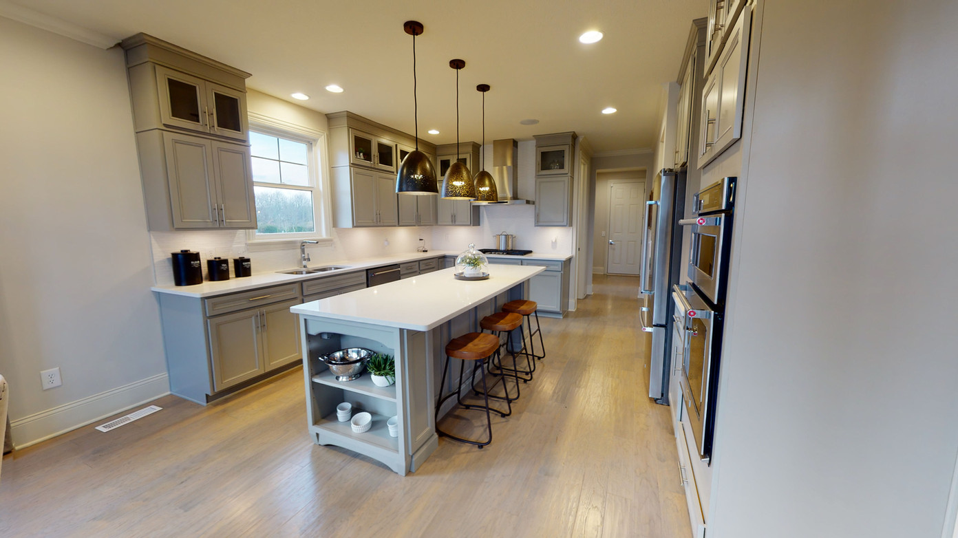 wide angle photo of beautiful modern kitchen with prep island, white countertops, and steel appliances