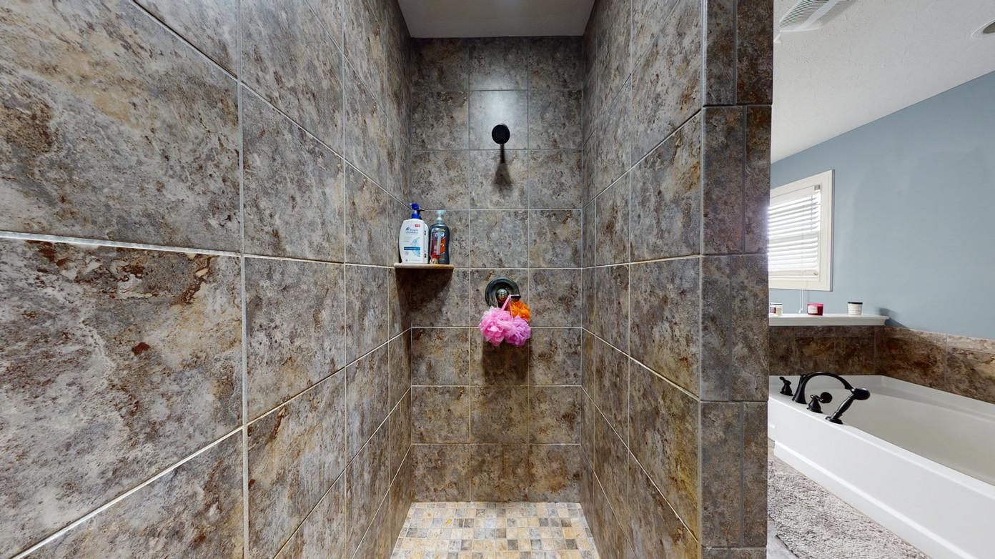 wide angle photo of dark brown granite taken inside of a shower.