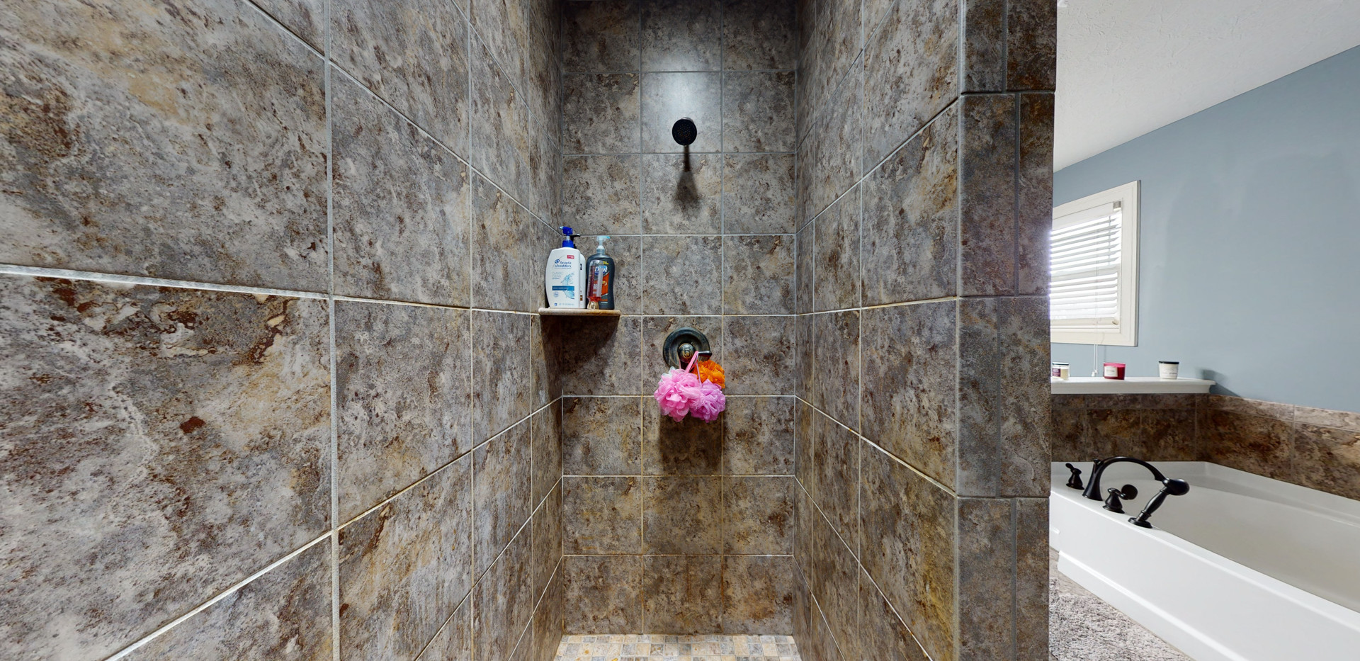 wide angle photo of dark brown granite taken inside of a shower.