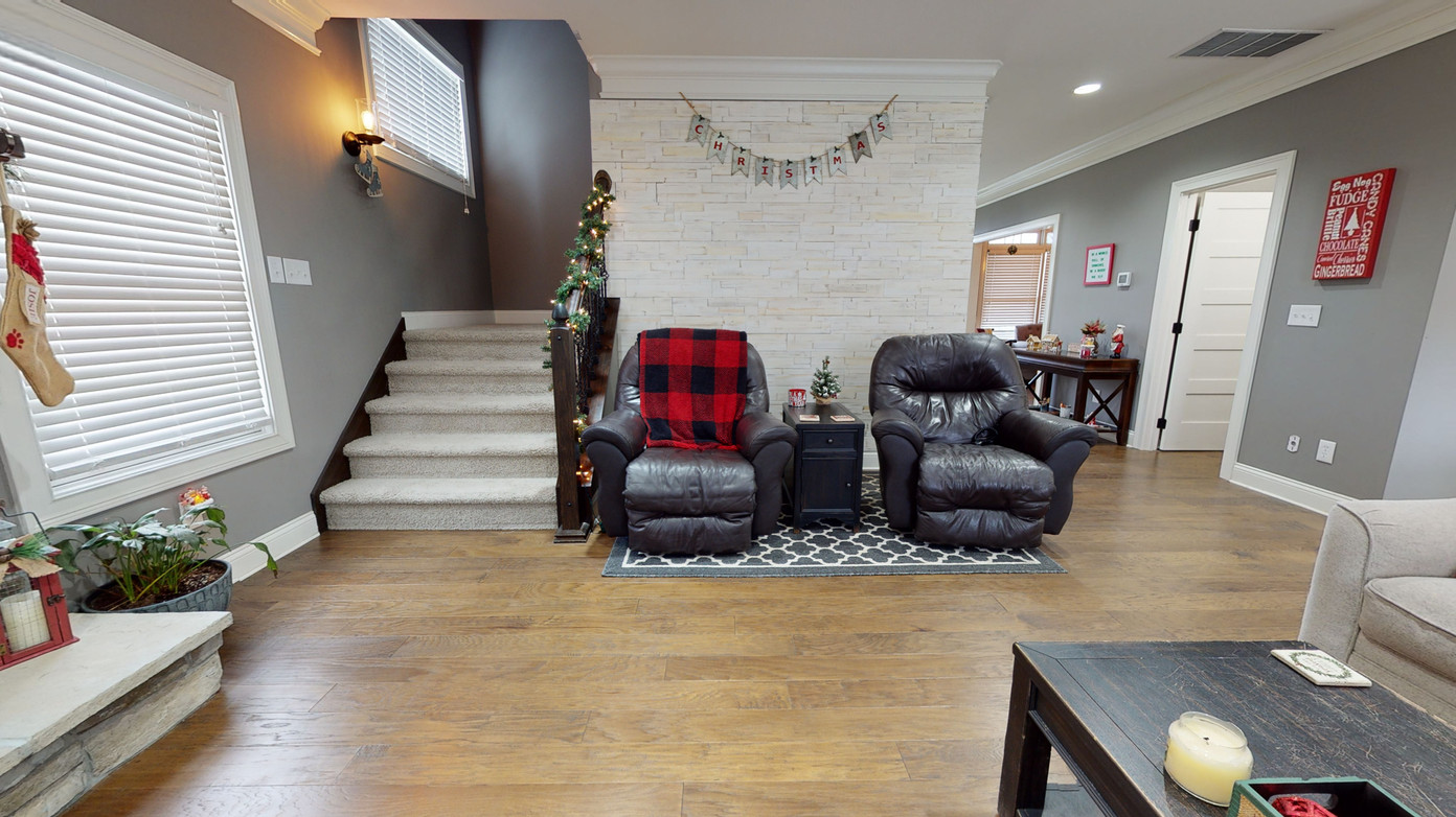 Black recliners on grey carpet and light natural brown wood floors showing stairs for second story.