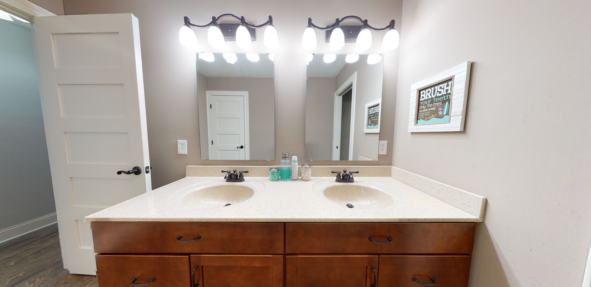 Beige bathroom with white countertops, beautiful wall lamps, and brown vanity.