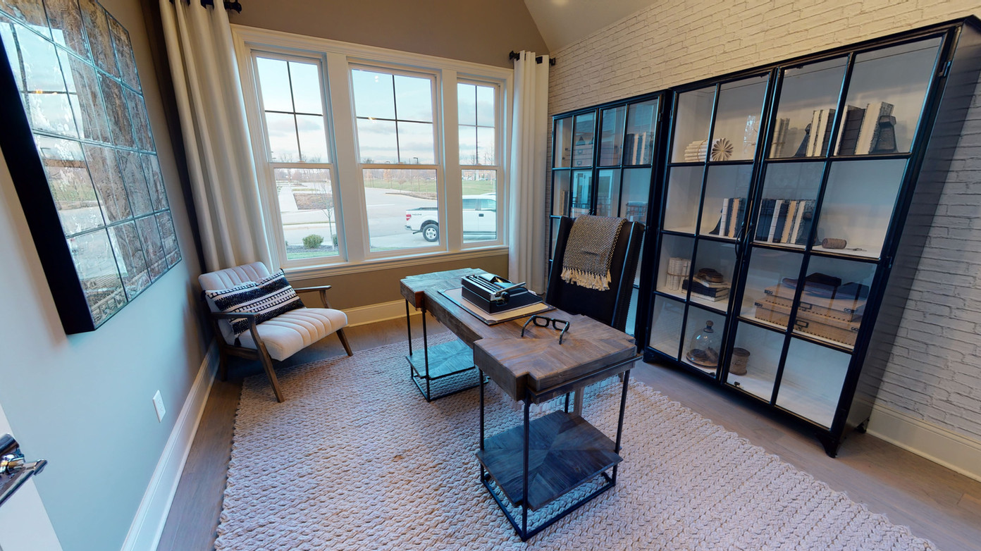well designed study or office area with black glass bookshelf, natural wood slap table, and modern rolling desk chair