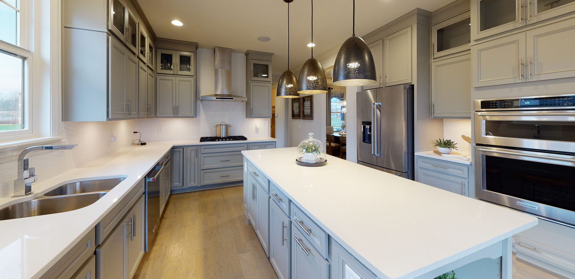 beautiful modern kitchen with prep island, white countertops, and steel appliances