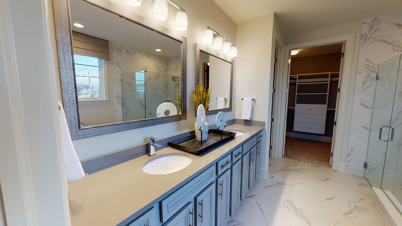 White marble bathroom with double grey vanity, double mirrors with grey frames, and large walk-in closet attached